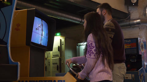 Guy and girl practice their skills on a car-racing slot machine in museum Footage