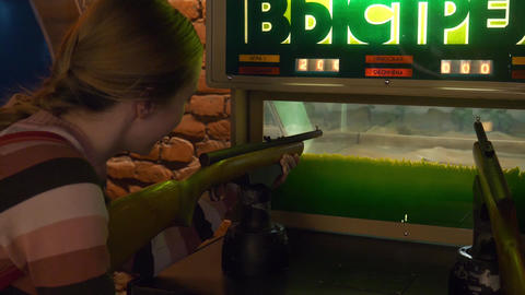 Pretty girl shoots with rifle in arcade game in museum of slot machines Footage