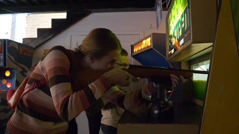 Young cute woman shoots with rifle in arcade game in museum of slot machines Footage