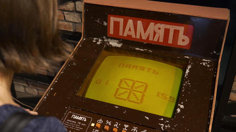Young woman plays memory testing arcade game with symbols in museum Footage