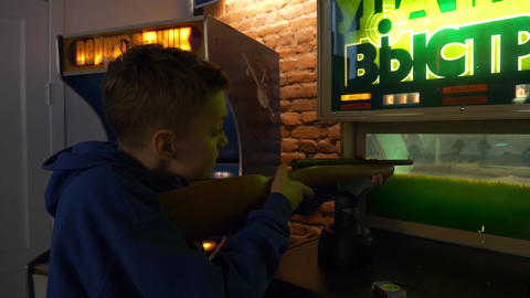 Cute boy shoots in rifle connected to old fashioned slot machines in museum Footage