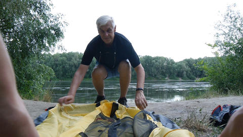 Elderly male retired tourist putting up tent. Green tourism, hiking Live Action