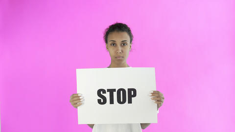Afro-American Girl Activist With Stop Poster on pink background Live Action