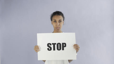 Afro-American Girl Activist With Stop Poster on grey background Live Action