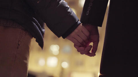 Two males are standing outside and holding hands in cold winter evening street Footage
