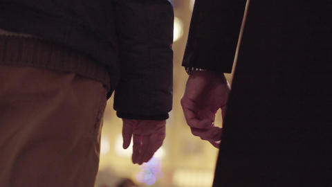 Two gay males are holding hands standing outside in cold winter street Live Action