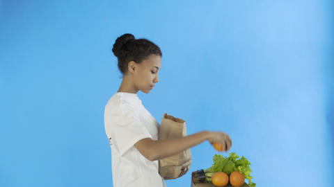 Happy woman load paper bag with organic healthy vegetables and fruits Footage