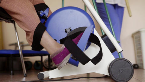 Legs are pedalling cycle ergometer as exercise for fitness testing in hospital Live Action