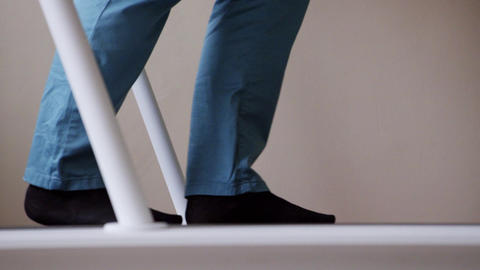 View of medical device track with person's legs slowl walking on it Footage