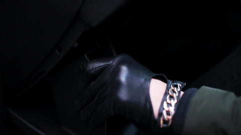 Person with black leather gloves opens car glove box and put some device in it Footage