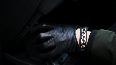 Hands wearing black leather gloves open glove box and put some device in it Live Action