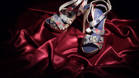 Approaching, pair of pair of blue high-heeled sandals standing on a red cloth Live Action