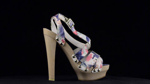 Rotation, sandals with high heels. Blue pink high heel shoes on black background Live Action
