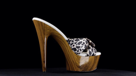 Rotation, high heel clogs. Leopard high heel shoes on black background Footage