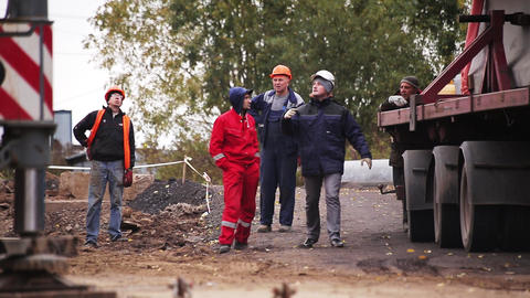 Group of construction workmen walk around, talk, discuss something outside Footage