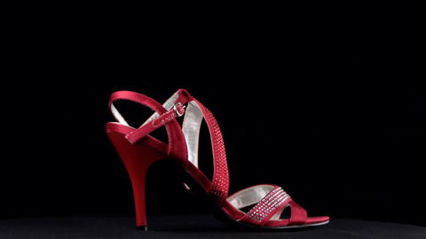 Rotation, sandals with high heels. Red high heel shoes on black background Live Action