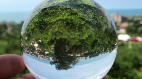 hand holding magic crystall ball over beautiful nature landscape, travel concept Live Action