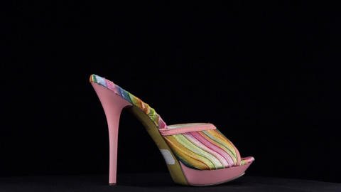 Rotation, high heel clogs. Pink high heel shoes on black background Live Action