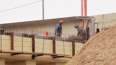 Scenery of male workers involved in action with hammer around concrete beem Footage