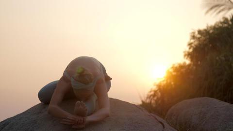 woman relaxes in janusirsasana asana on big rock slow motion Footage