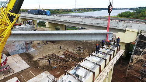 Active bridge construction process with two cranes nearby roadway and river Footage