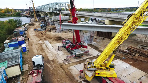 Active bridge construction at area with two cranes nearby road and river Footage