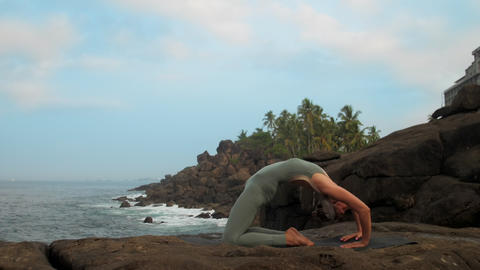 yoga practitioner changes hands position at sea slow motion Footage