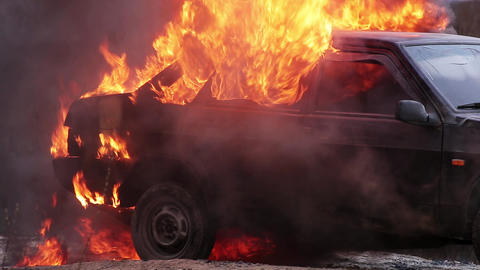 Massive orange flame of fire totally burns dirty old car left on deserted road Live Action