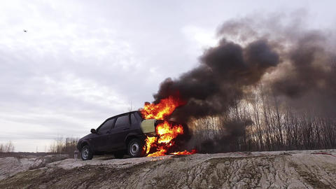 Huge smoking flame of fire completely burns dirty old car left on deserted road Live Action