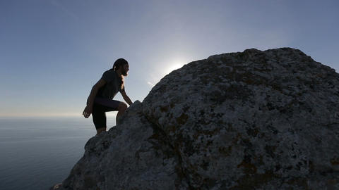 Mountaineer reaches the summit. Man climbs a mountain an celebrates the Footage