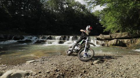 Bolechov, Ukraine - July 12, 2019: Extreme motorcyclist rides near river Footage