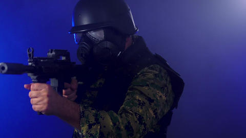 Soldier wearing gas mask pans rifle in thick smoke Live影片