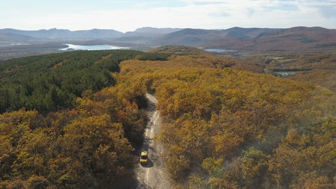 Aerial view of car driving through the forest in mountains. Driving on beautiful Footage