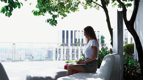 Attractive girl working on laptop outdoors Footage