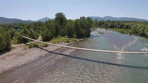 Aerial view of suspension wooden bridge above the mountain river Live Action