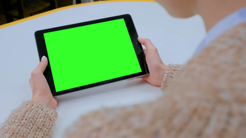 Woman looking at tablet computer with green screen at home Live Action