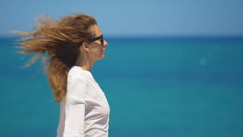 Young woman standing on top of the high cliff above the sea, raising her hands Footage