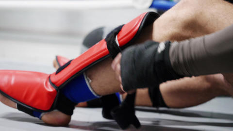 Athlete boxer man fighter in sportswear tying bandage shield on legs before Footage