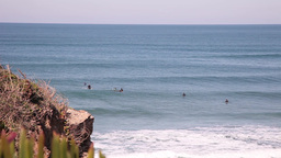 rocky beach with surfers in water Footage