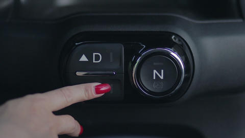 Woman hand pushing reverse gear button in car Footage