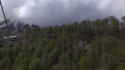Dull forested mountain edge, low cumulus clouds, aerial view from gondola lift Footage