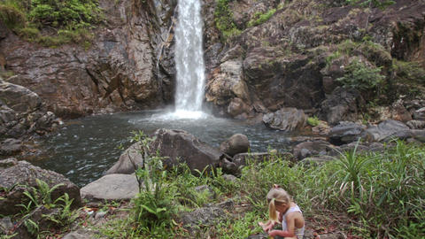 Little Girl Sits on Stone against High Waterfall Cascade Footage