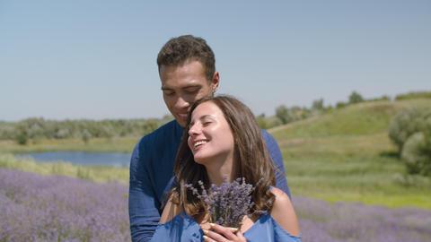 Loving couple bonding in blooming lavender field Footage