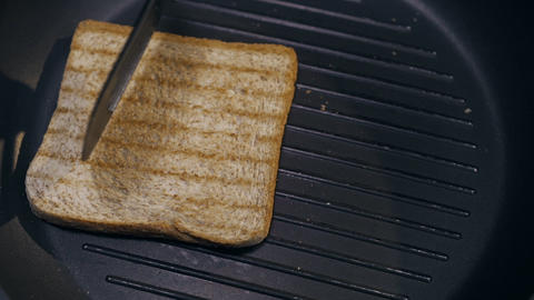 The cook turns toast from side to side on the hot grilling pan, making the Live Action
