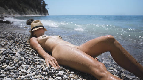 Young woman relaxing on nudist beach on summer vacation Footage