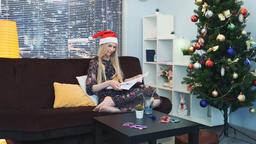 Elegant woman in Santa hat reading book sitting on sofa on Christmas Footage