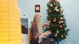 Profile view of nice lady hanging toys on Christmas tree Footage