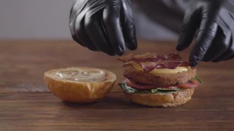 Hands of the chef making burger close-up. The cook putting becon and onion on Footage