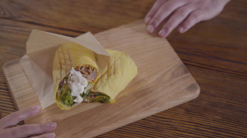 Tasty shawarma with sauce lying on the wooden board. Male and female hands Footage
