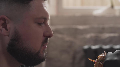 Close-up portrait of a bearded man in black gloves eating a tasty burger. The Footage